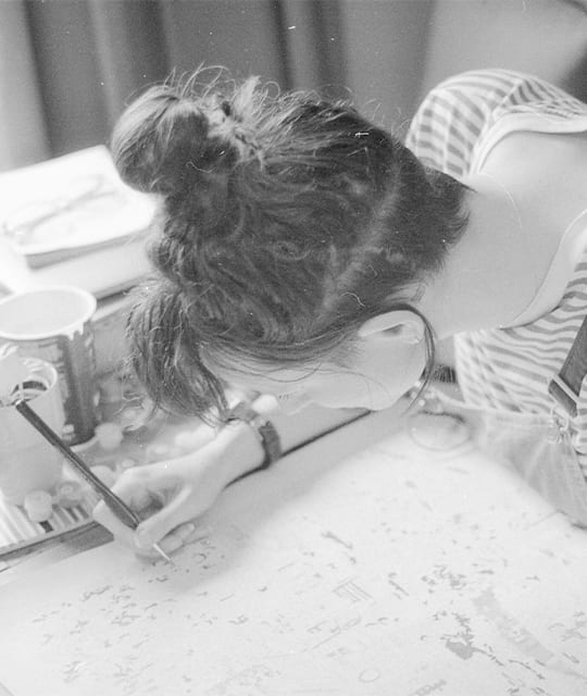 Woman doing a paint by numbers in black and white
