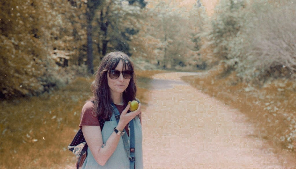 Woman on woodland path eating an apple